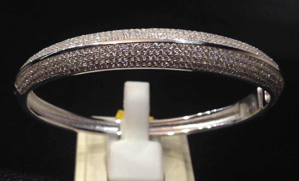 Sterling Silver Bangle- openable with C.Z stones. This sturdy yet elegant piece that dazzles with micro setting of zirconia has a smooth finish and a button type secure locking. It has a non-tarnish Polish that is consistent with white gold finish.