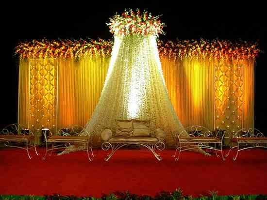 backdrop with yelloish lights and candle stands.. rings made by real mongra flowres...  - by Global Star Events, Jaipur