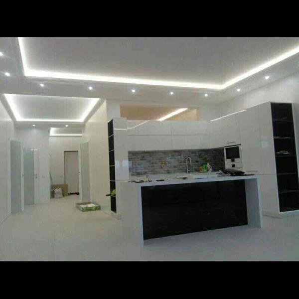 Modular kitchen with white kitchen tiles.