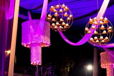 Candle stand hung on the roof along with chandeliers of mogra and rose tassels......Really candles add beauty to any decor. - by Super Tent House, New Delhi